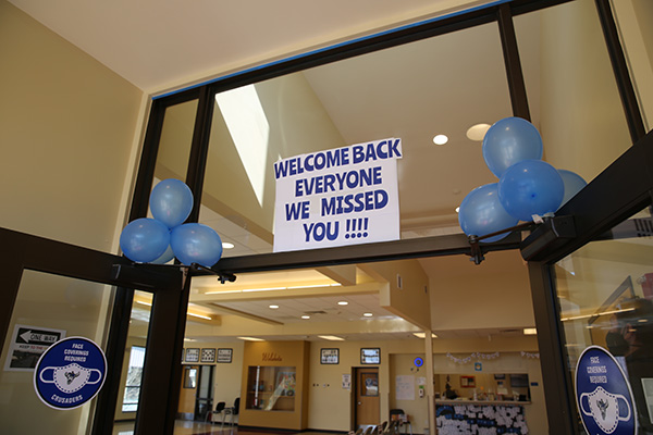 """painted sign that reads """"welcome back everyone, we missed you"""""""