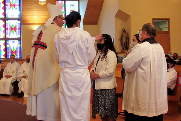 Red Cloud Priest performing confirmation on a young lady